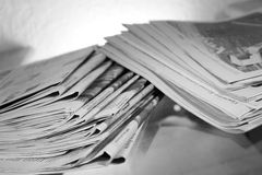Stack of Newspapers on Table with Backlight (B&W). Stack of newspapers on a table against a white wall. (B&W Royalty Free Stock Photography