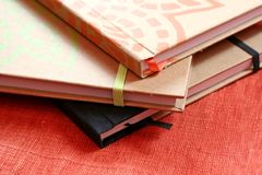 Stack of Notebooks. Three colorful notebooks on orange background stock photography