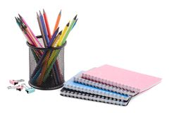 A stack of notebooks, colored pencils in a black cup and several clips for papers. The concept of education. Royalty Free Stock Image