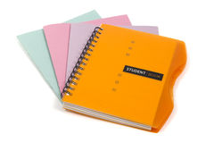 Stack of notebooks. Orange diary lying on a stack of of multicolored school notebooks isolated on white background Stock Images
