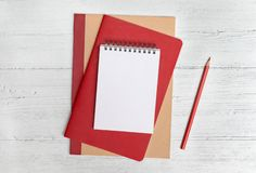 Stack of notebooks and a red pencil on a white wood background. Flat lay with copy space stock photos