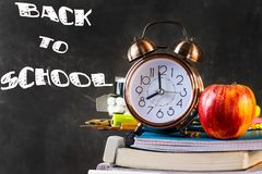 Stack of notebooks, textbooks, pads, pencils, supplies with alarm clock red apple on top. Black chalkboard. Stock Photography