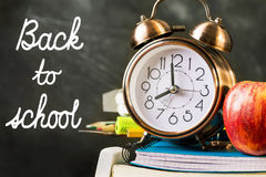 Stack of notebooks, workbooks, pads, pencils, supplies with alarm clock red apple on top. Back to school hand lettering on chalkbo Stock Image