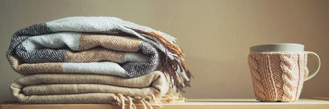 Stack Of Beige Checkered Wool Blankets And Cup On A Wooden Chest. Autumn Concept Royalty Free Stock Photography