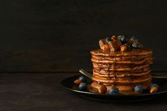 Stack Of Chocolate Pancakes With Icing, Blueberry, Almond, Hazelnut And Pieces Of Chocolate. Stock Photography