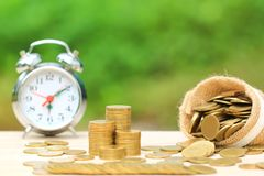 Free Stack Of Gold Coins Money Spilled From The Bag And Alarm Clock On Green Background, Saving Money For Prepare In Future And Stock Images - 139293184