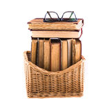 Stack of old antique books in a wicker basket and spectacles lying on top Stock Images