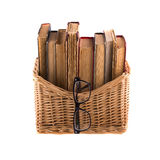 Stack of old antique books in a wicker basket and spectacles in thick-rimmed Stock Image