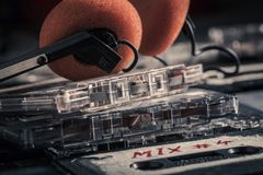 Stack of old audio cassettes and headphones. On old table stock images