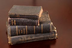 Stack of old bibles including German bibles. Resting on a table awash in warm light Stock Image