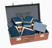 Stack of old blue books in brown suitcase Stock Photos