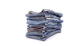 Stack of old blue jeans isolated on white Stock Photos