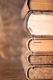 Stack of old books. Stack of antique aged books on wooden table and background with interesting texture on butts Stock Photography