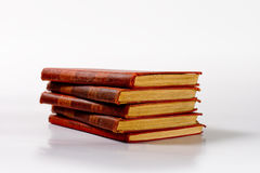 Stack of Old Books. Isolated stack of old books reflecting on white glossy surface Royalty Free Stock Photography