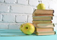 Stack of old books. Apple on a white brick wall background. School concept, education stock photography
