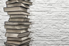 A stack of old books on the background of brick wall Stock Photography