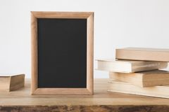 Stack of old books and blackboard in frame on wooden table on white stock photo