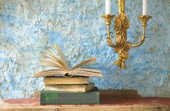 Stack of old books. Candleholder, free copy space Stock Photos