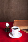 Stack of old books, cup of coffee, and ancient candle on the red Royalty Free Stock Photography