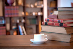 Stack of old books and cup with coffee over wooden table, retro filtered image Stock Photo
