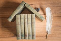 Stack of old books forming the figure of a house. Stack of old books forming the figure of a house, with an inkwell like a fireplace and a feather like a tree Royalty Free Stock Photography