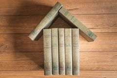 Stack of old books forming the figure of a house. Stack of old books forming the figure of a house on some wooden boards Royalty Free Stock Image