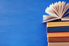 stack of old books in front of blue wooden background Royalty Free Stock Photos