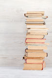 Stack of old books. In front of wooden wall. School background. Education backdrop Royalty Free Stock Image