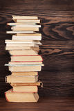 Stack of old books. In front of wooden wall. School background. Education backdrop Stock Image