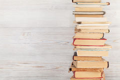 Stack of old books. In front of wooden wall. School background. Education backdrop Stock Photo