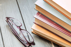 A stack of old books and glasses for reading Stock Photo