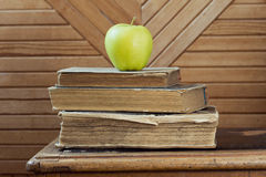 Stack of old books and green apple  on old chair. Stack of vintage  books and green apple  on old chair Royalty Free Stock Photo