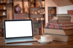 Stack of old books and laptop over wooden table Stock Photo
