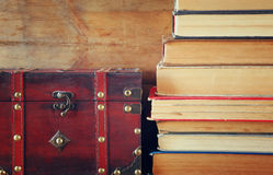 Stack of old books next to antique wooden chest on wooden shelf. vintage filtered Stock Images