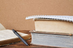 Stack of old books, notebook, opened book with pen on wooden tab Stock Photography