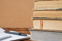 Stack of old books, notebook with pen on wooden table Stock Photos