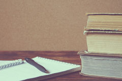 Stack of old books, notebook with pen on wooden table. Concept of education. Vintage tone Stock Photos