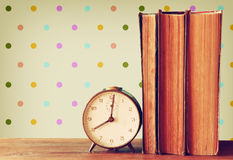 Stack of old books and old clock over wooden table and retro style wallpaper Royalty Free Stock Images