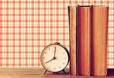 Stack of old books and old clock over wooden table and retro style wallpaper Royalty Free Stock Photography
