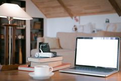 Stack of old books, open laptop and old camera over wooden table, retro filtered image Stock Photos