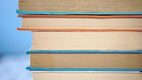 Stack of old books are piled on an old wooden table. On a bright blue background. Close-up. Camera moves up stock video