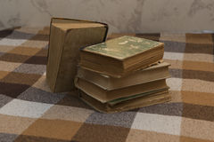 Stack of old books on a plaid. Stack of battered old books on a plaid Stock Image