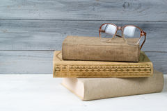 Stack of old books and reading glasses on wooden background Royalty Free Stock Photography