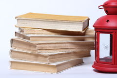 Stack of old books. red lamp with candle Royalty Free Stock Images