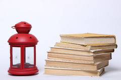 Stack of old books. red lamp with candle Royalty Free Stock Photo