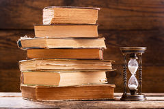 Stack of old books and retro hourglass stock photography