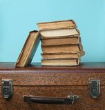 Stack of old books on retro suitcase on a blue background. Stack of old books on retro suitcase on a blue background royalty free stock photo