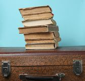 Stack of old books on retro suitcase on a blue background. Stack of old books on retro suitcase on a blue background royalty free stock photography