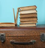 Stack of old books on retro suitcase on a blue background. Stack of old books on retro suitcase on a blue background stock images