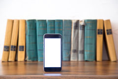 Stack of old books and smartphone over wooden table, retro filtered image Royalty Free Stock Photos